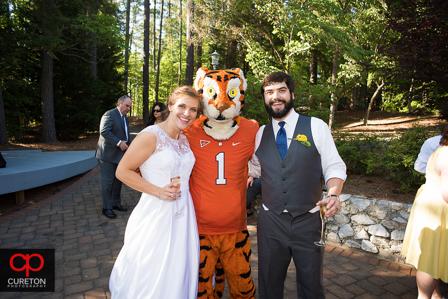 The bride and groom pose with the Clemson Tiger.
