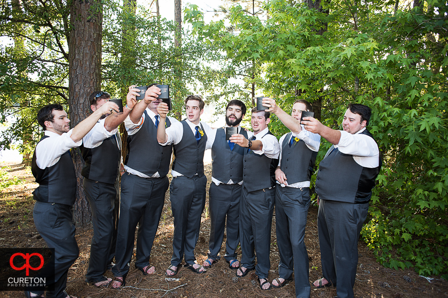 The groom and his groomsmen toasting with their flasks.