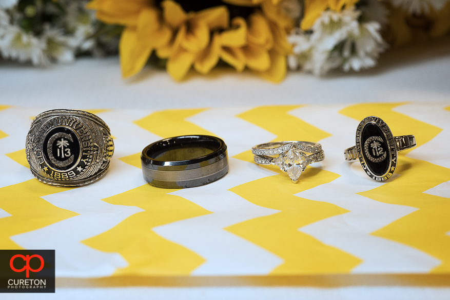 The wedding rings and their Clemson class rings together.