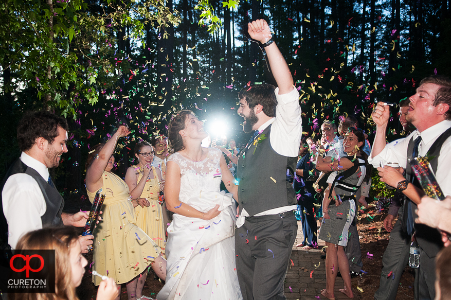 The bride and groom leaving under confetti cannons as they leave their wedding reception.
