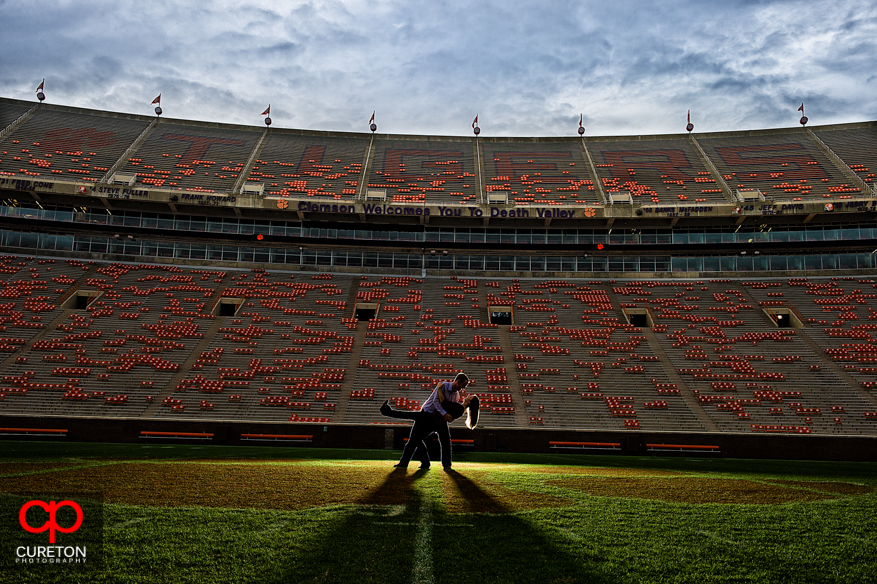 A couple dancing on the 50 yard line in Death Valley (Clemson Memorial Stadium) during an engagement photo session.