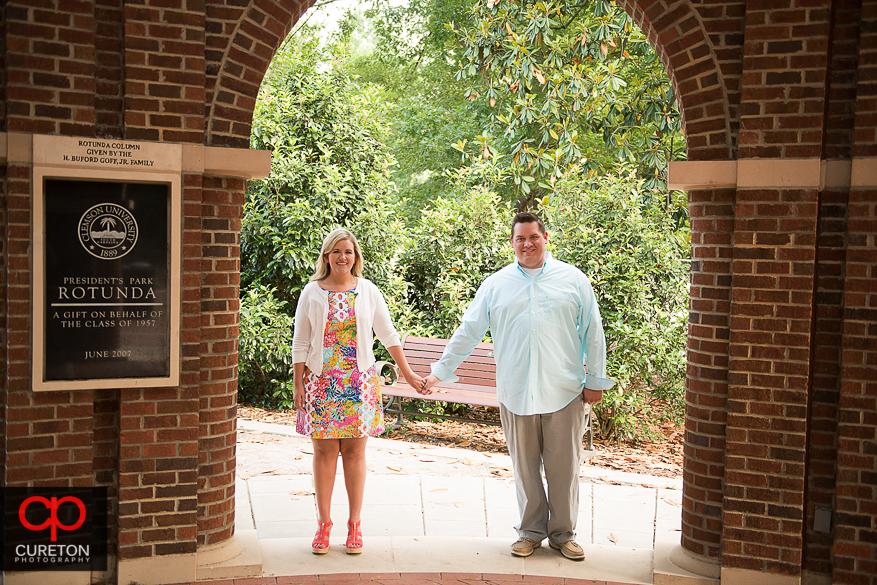 Engaged couple walking holding hands through the rotunda.