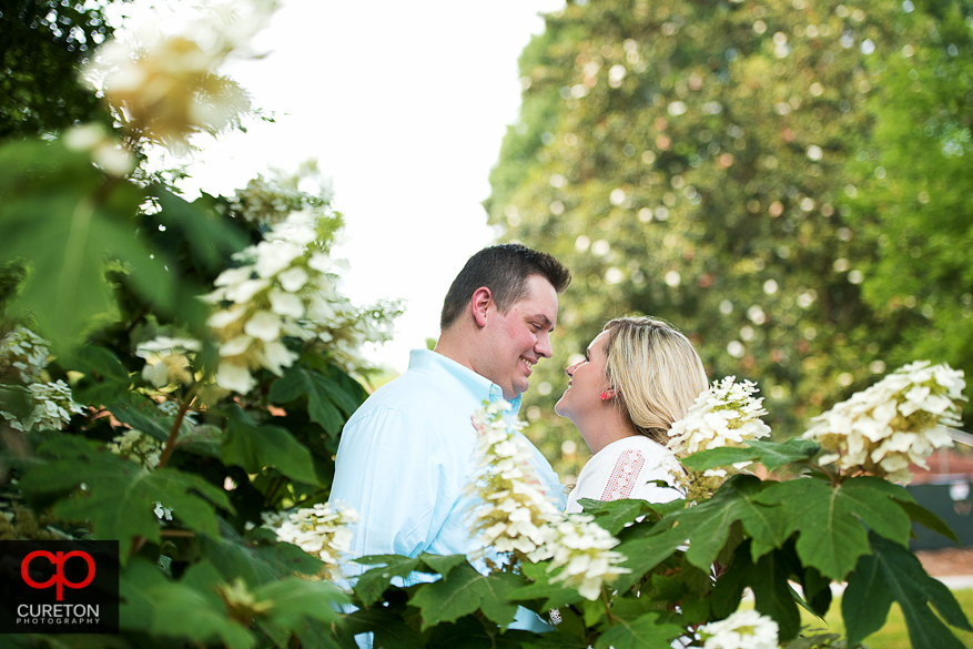 Engaged couple standing in the middle of flowers on the Clemson university campus