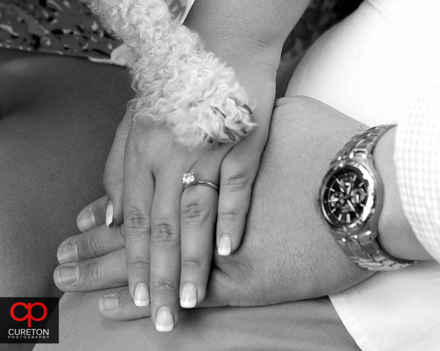 Engaged couples hands along with their dog's paw showing the ring.