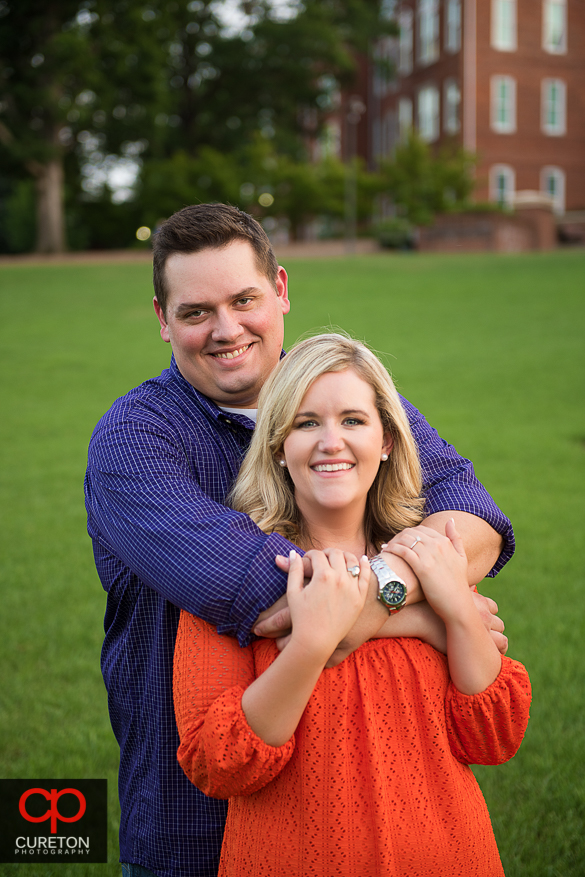 Couple hugging during an engagement session at Clemson University.