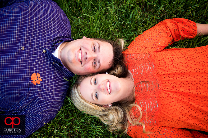 Couple laying on the grass during an engagement session at Bowman Field in Clemson.