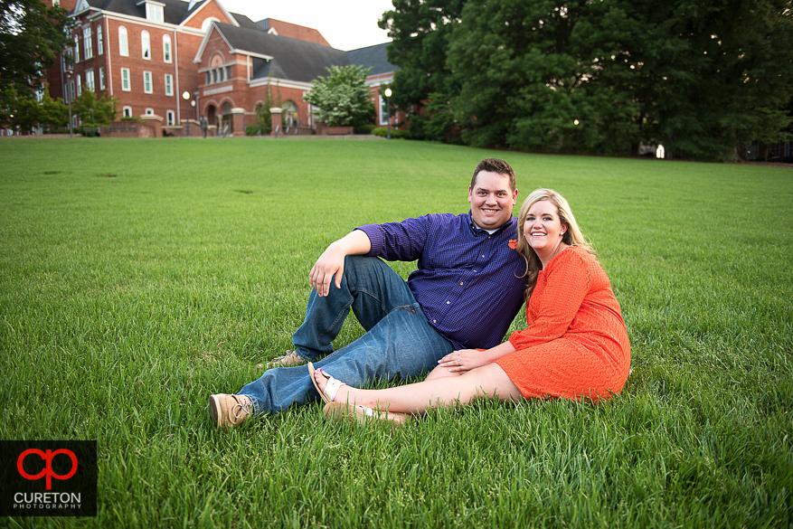 Engaged couple sitting on Bowman Field.
