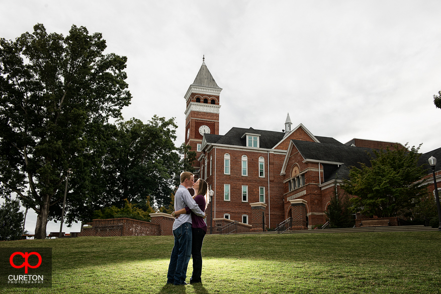 A couple kissing on Bowman field with Tillman Hall in the background during an engagement session in Clemson, SC.