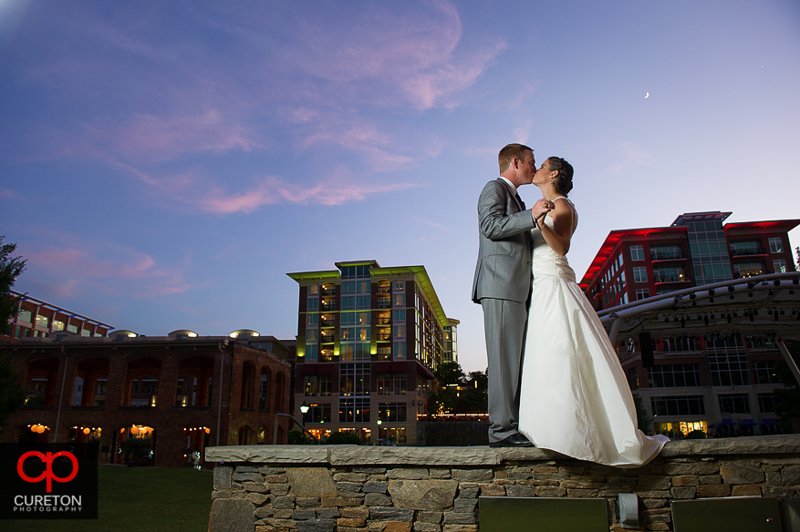 Married Couple kissing in downtown Greenville,SC outside their Huguenot Loft reception.