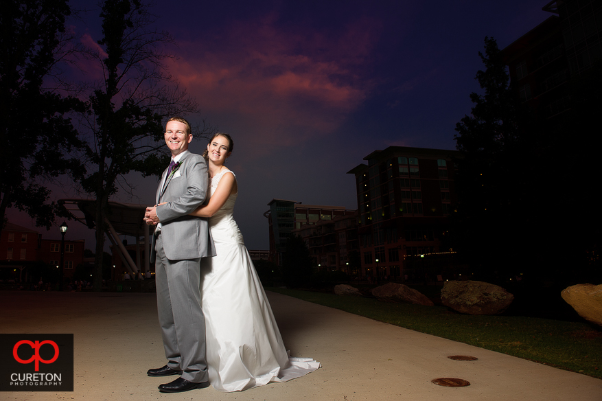 Couple posing at sunset in downtown Greenville outside their Huguenot Loft wedding reception.