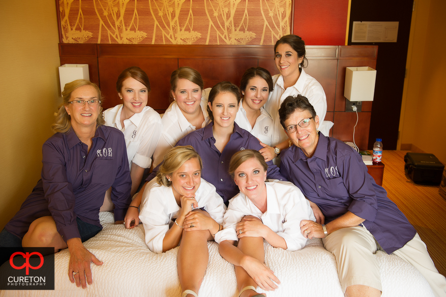 The bride and her bridesmaids all on a bed.
