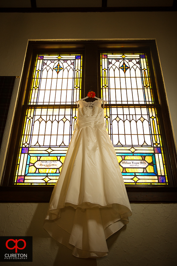 Bride's dress hanging in front of a stained glass window.