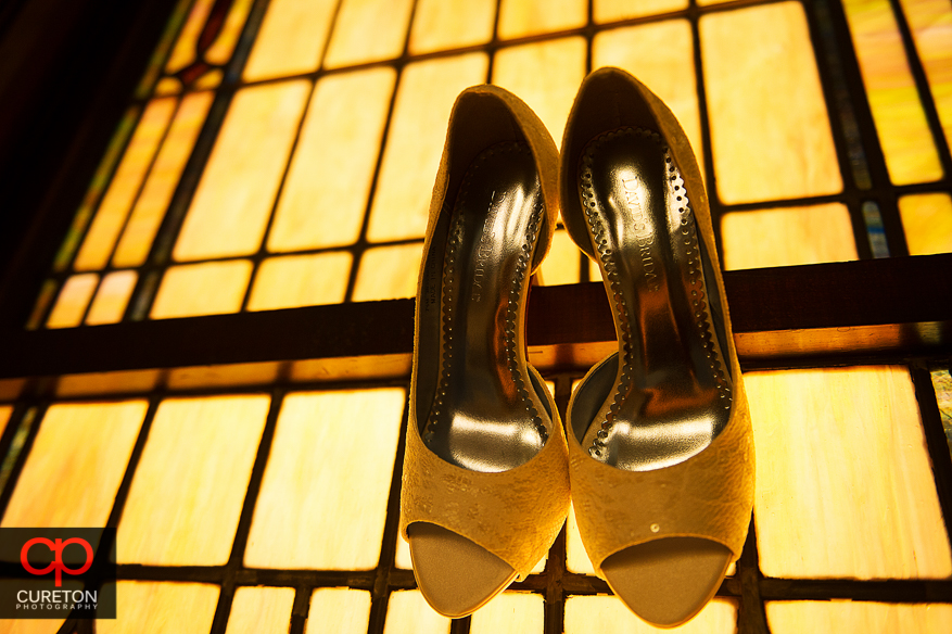 The bride's shoes hanging in front of a stained glass church window.