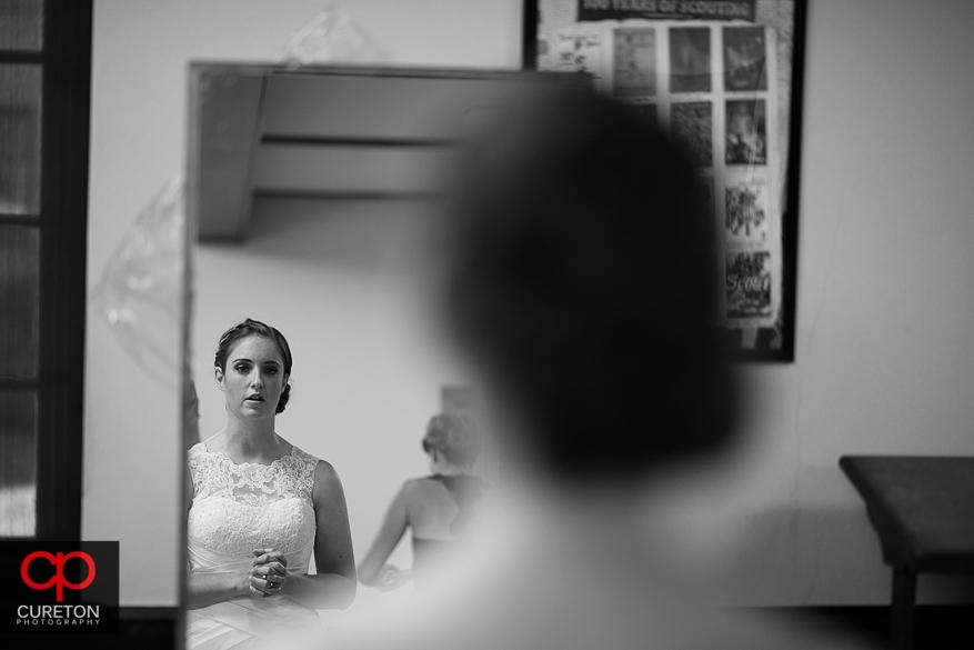 The bride looking into a mirror.
