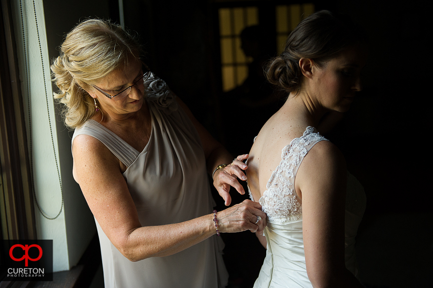 The bride's mother helps her into the dress.