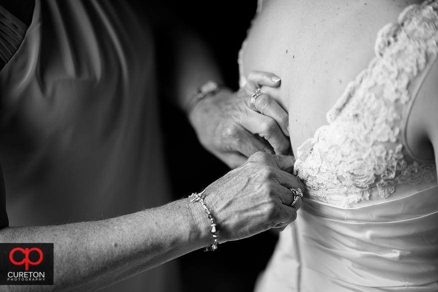 The brides mother's hands helping zip her dress.