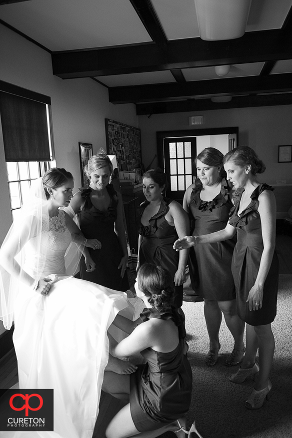 The bridesmaids all helping the bride get ready.