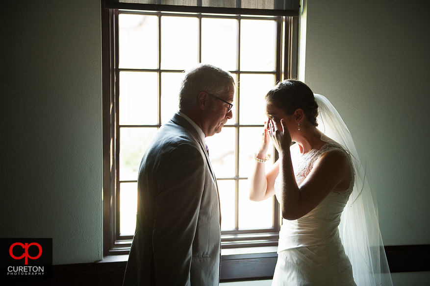 The bride wipes tears from her eyes as her dad sees her for the first time.