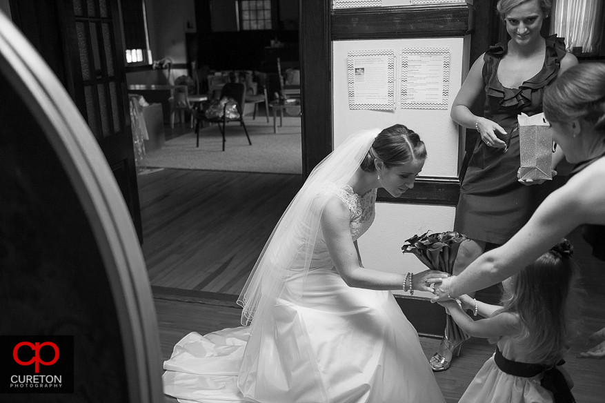 The flower girl hands the bride some flowers.