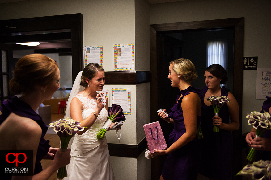 The bride cries as she receives her groom's gift.