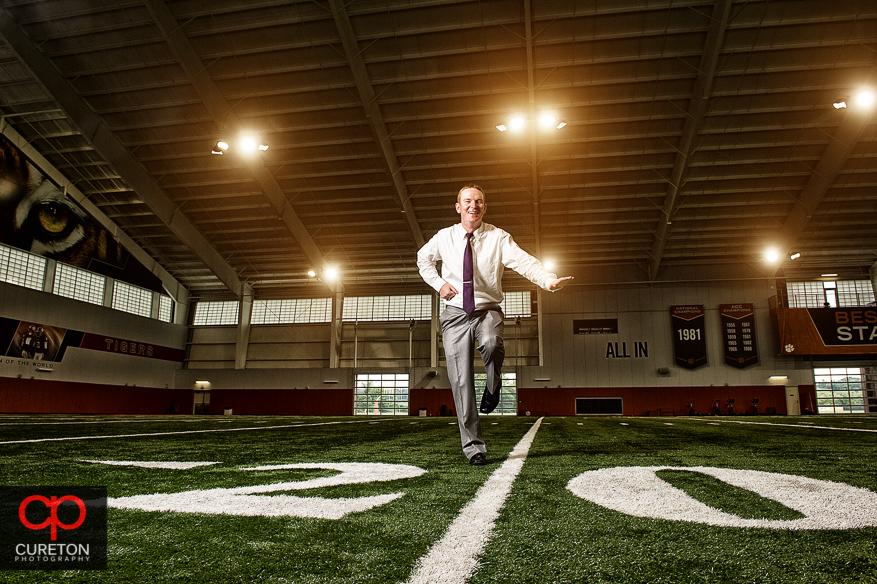 The groom doing hi heisman pose in the Clemson football indoor complex.