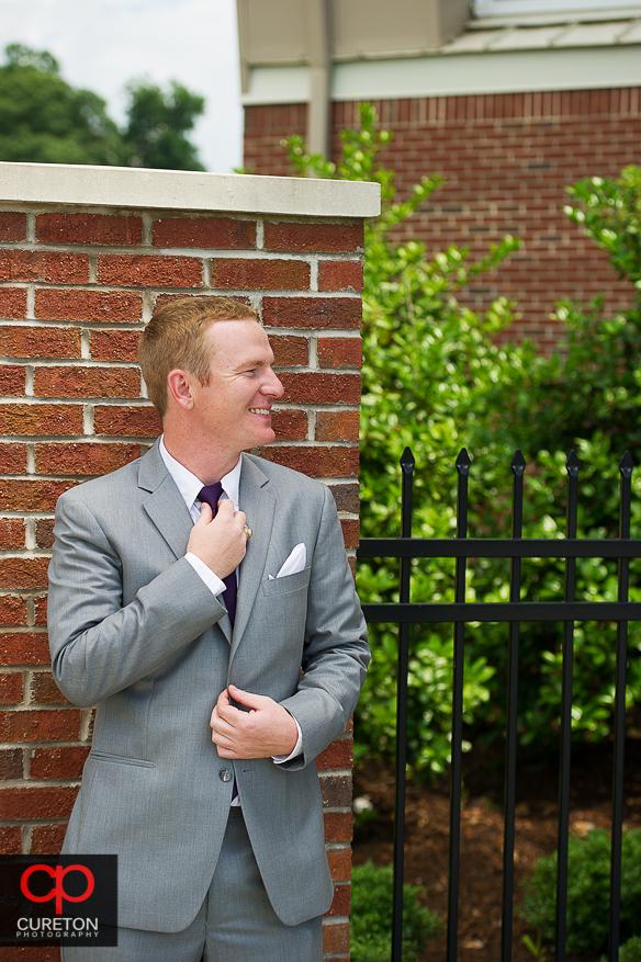 The groom adjusts his tie.