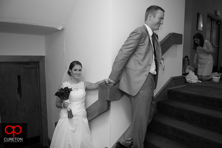 The bride and groom hold hands around a corner before the wedding.