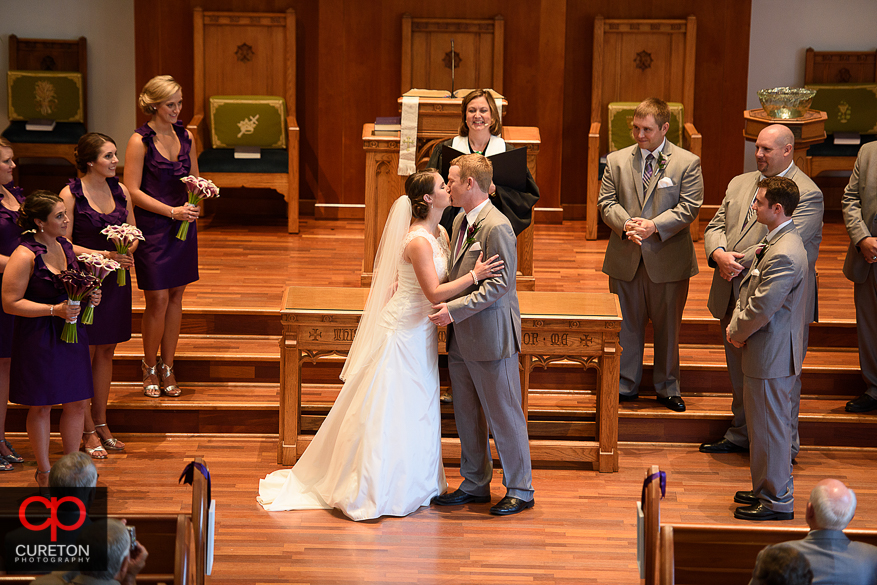 The bride and groom share a first kiss at their wedding.
