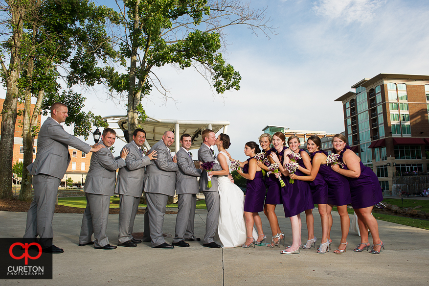 Bride and Groom pushed together by the wedding party.