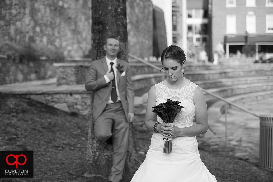 The bride looks at her flowers while the groom stands in the distance.
