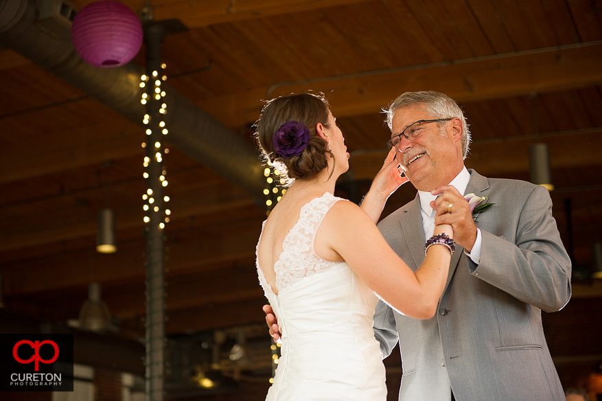 The bride wipes tears from her fathers eyes during their dance.