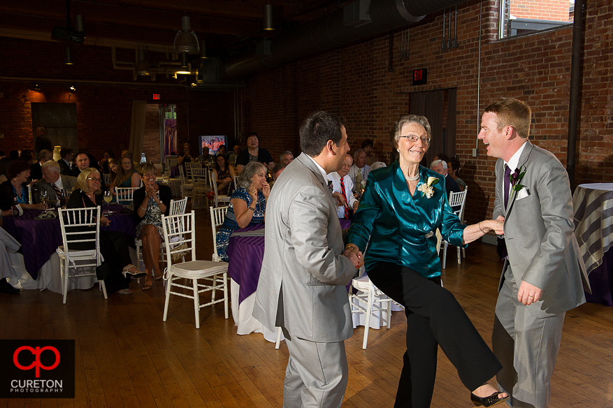 The groom dances with his grandmother.