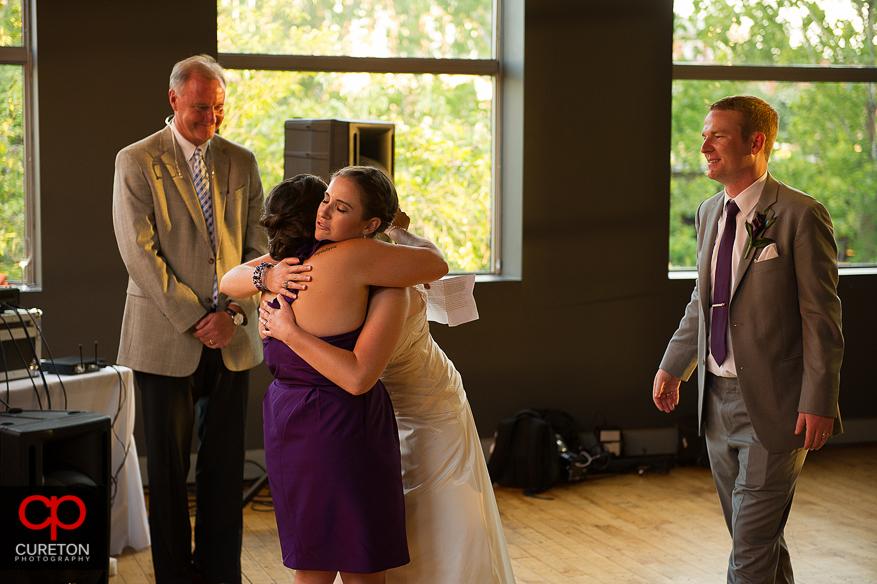 The bride hugs her bridesmaid.