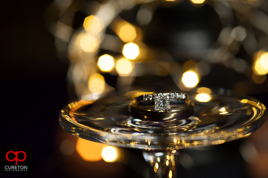 Wedding ring close up with light sin the background.
