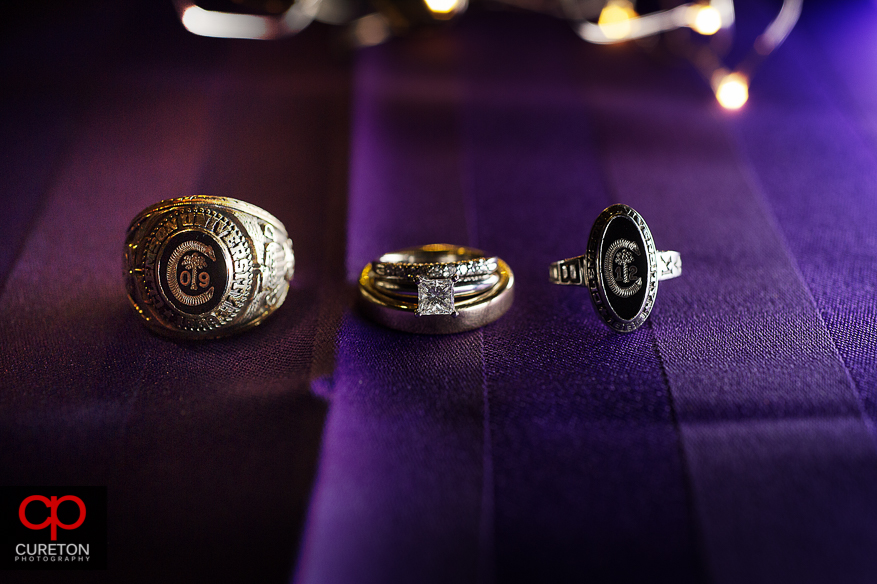 Creative shot of the bride and grooms wedding rings and Clemson college rings.