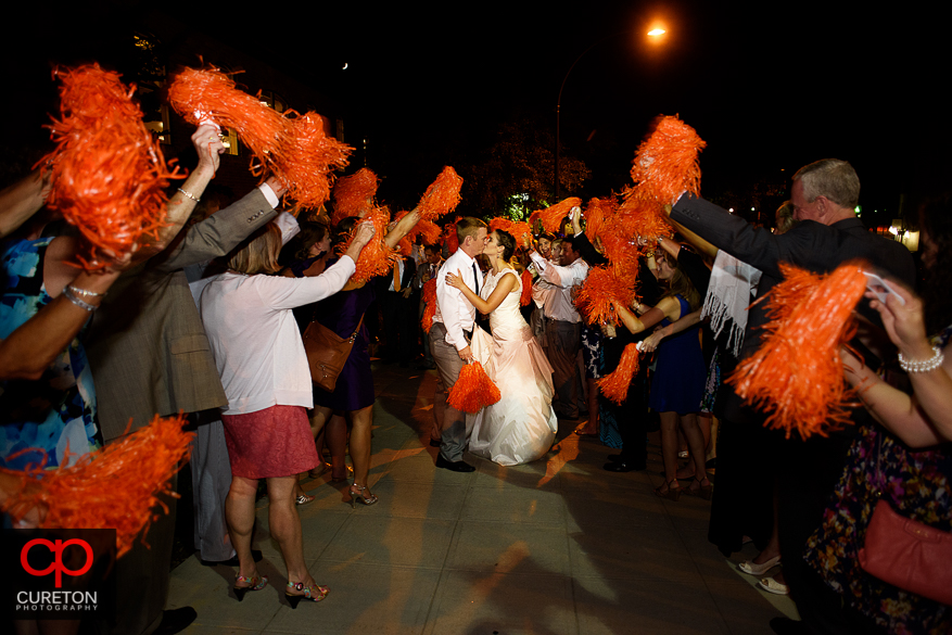 The bride and groom leave while the guests shake Clemson shakers.