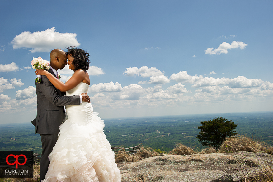 A married couple standing on the rocks after their wedding at the Cliffs of Glassy Chapel.