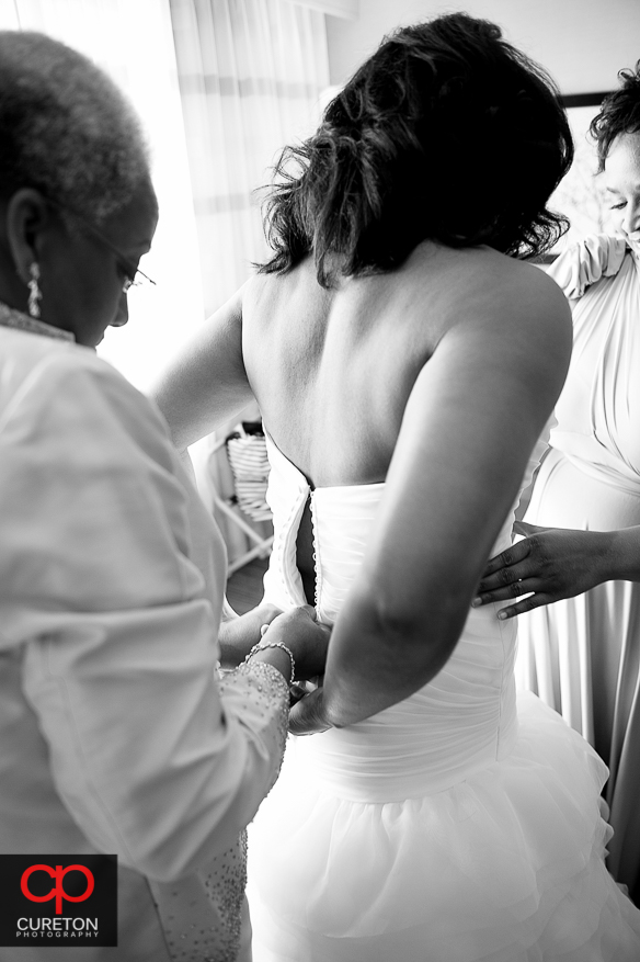 The brides mom helping her into her dress.