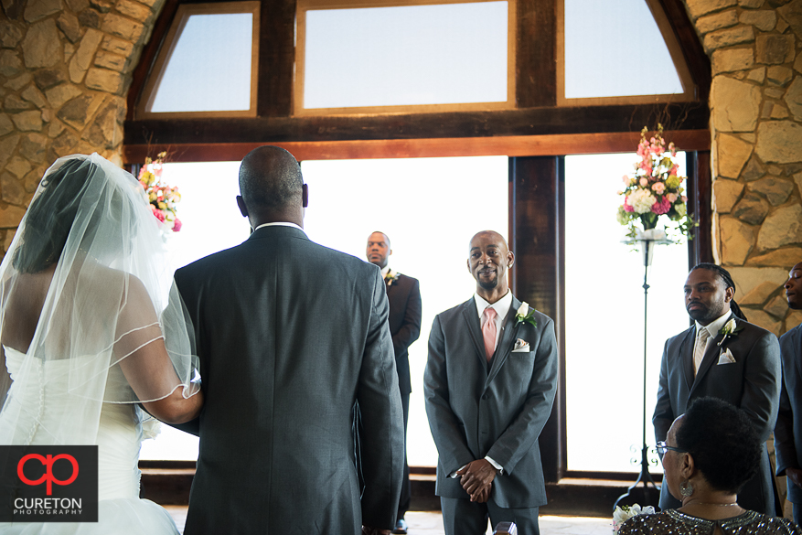 Groom smiling as his bride walks down the aisle at Glassy Chapel.