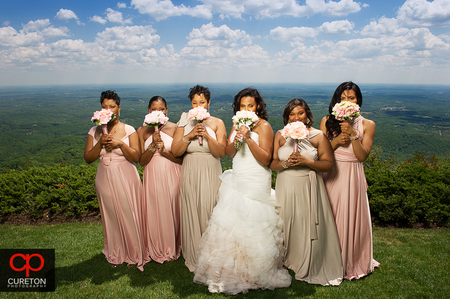 Bridesmaids holding flowers in front of their faces.