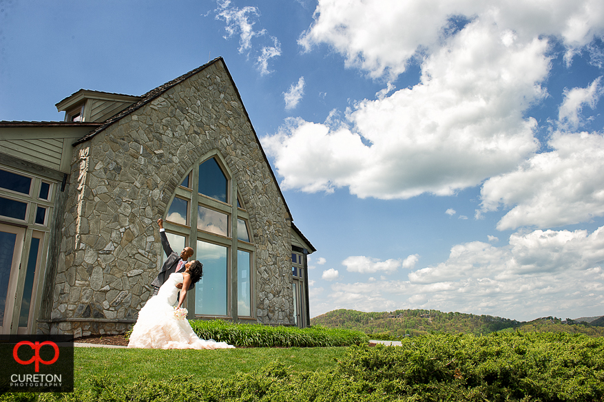 Groom does super hero pose after his wedding at Glassy Chapel..