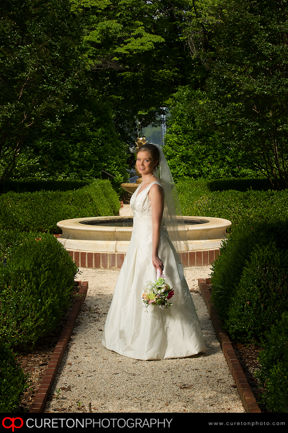 Bride standing in front of fountain.