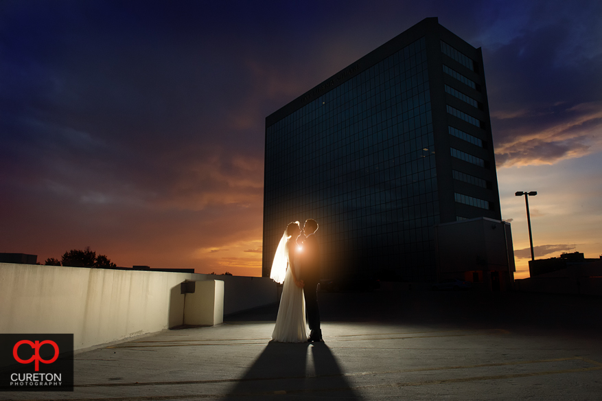 Bride and Groom at sunset with the One Liberty Square building in the background.