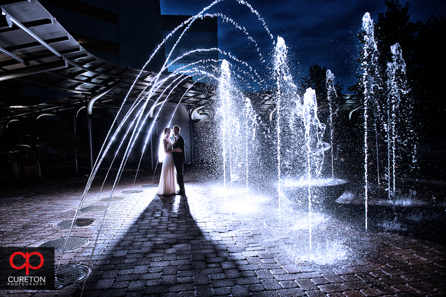 Creative photo of a bride and groom their Commerce Club wedding in Greenville,SC playing in the fountain.