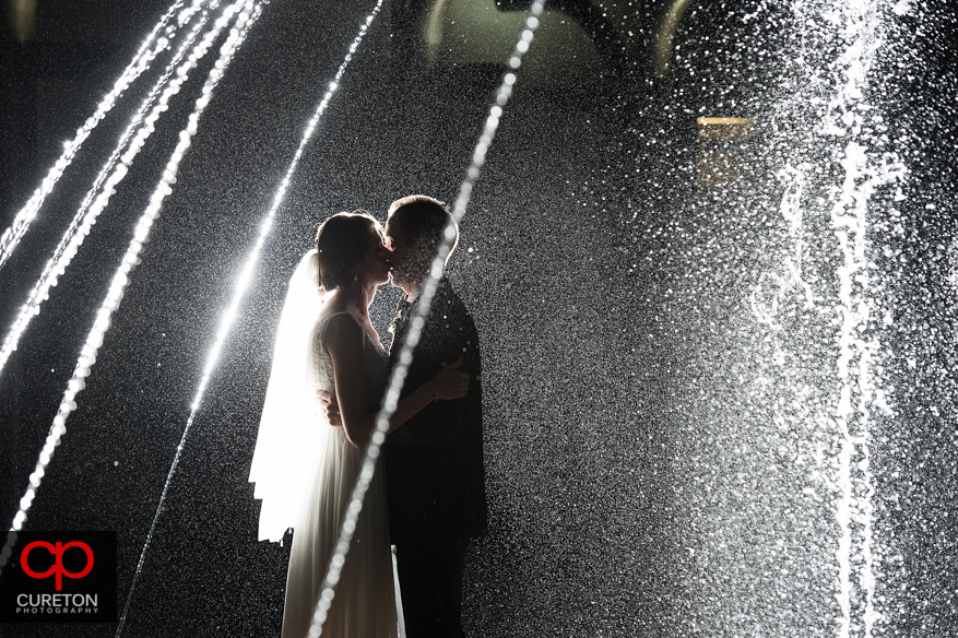 Backlit shot of bride and groom in a fountain.