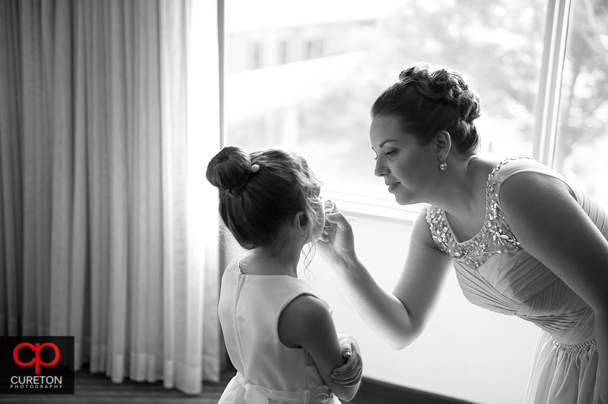 A bridesmaid helps put makeup on the flower girl.