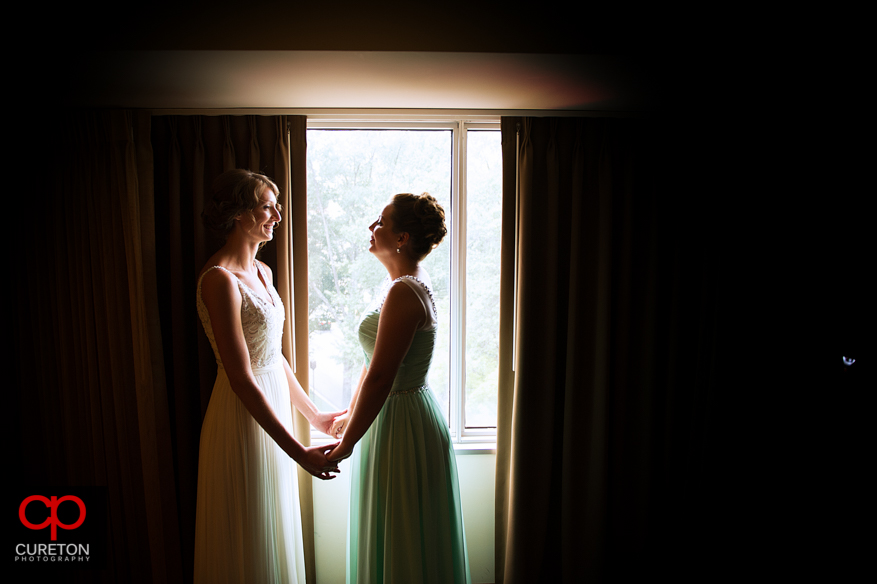 The bride and her maid of honor share a moment in front of the window.