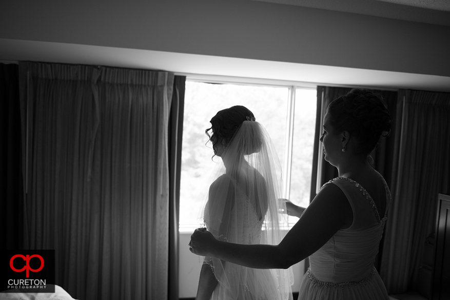 The bride getting her veil put on.