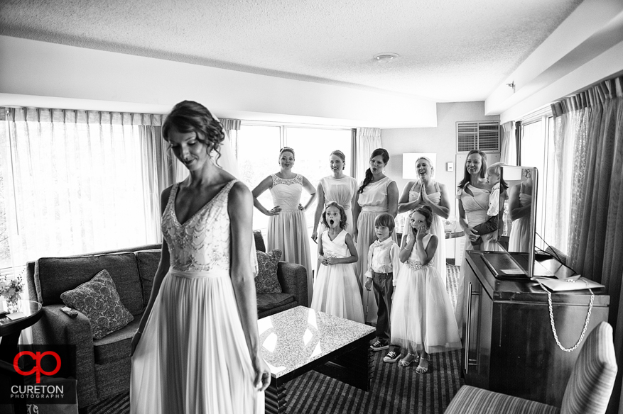 The bride reveals herself to her bridesmaids.