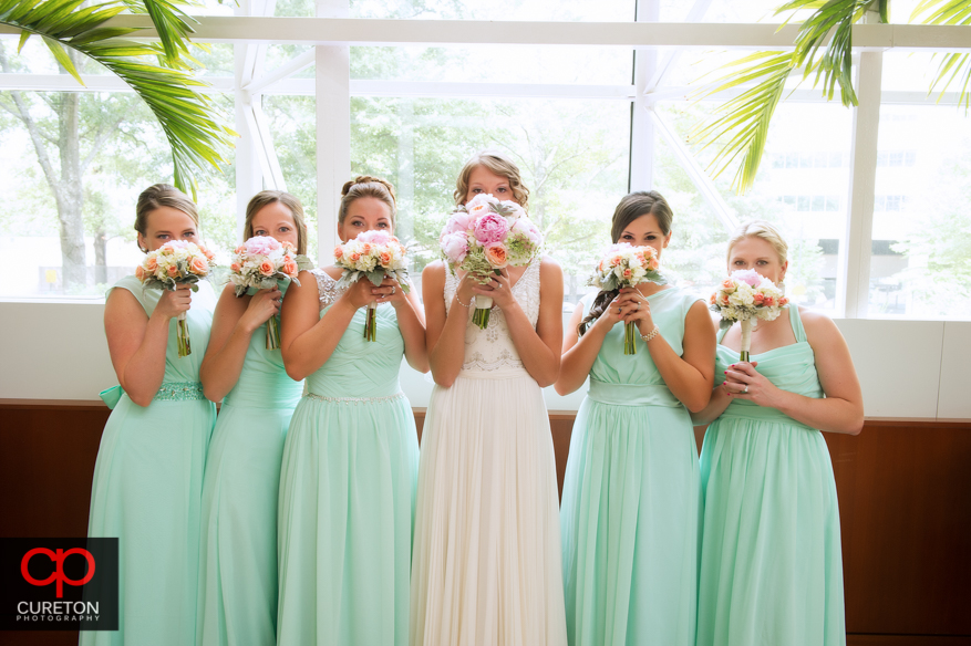 Bride and bridesmaids with flowers in front of their face at the downtown Hyatt regency before the wedding.